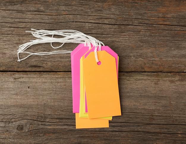 Impila le etichette di carta di colore vuote legate con lo spago bianco. cartellino del prezzo