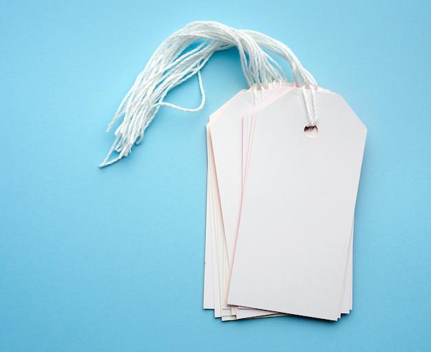 Pila di etichette di carta rettangolari bianche vuote su una corda