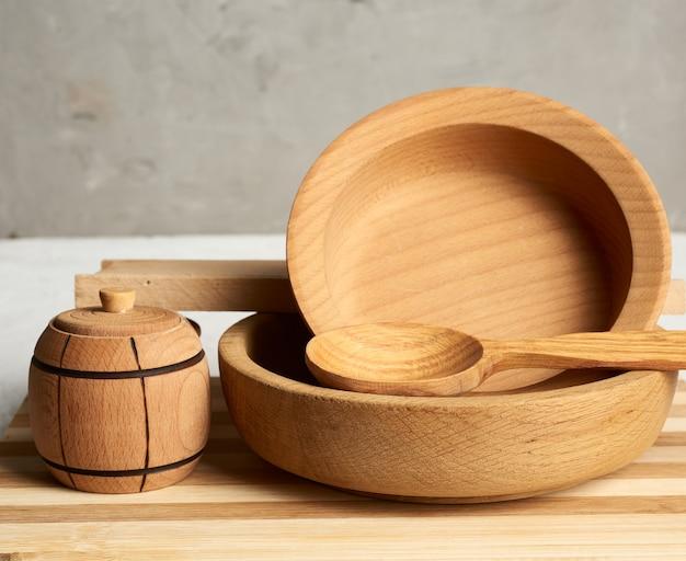 Pila di piatti rotondi di legno vuoti e nuovo tagliere su gray