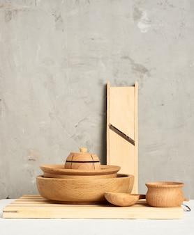 Pila di piatti rotondi in legno vuoti e nuovo tagliere