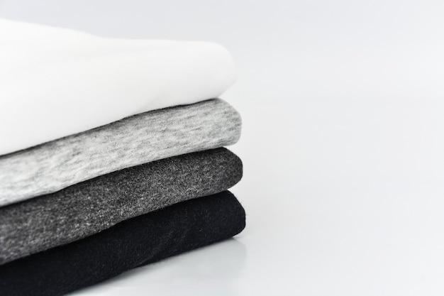Pila di tshirt monocromatica piegata nera grigia e bianca su sfondo bianco