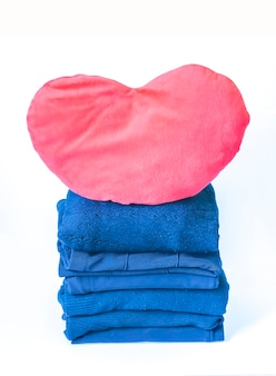 Pila di vestiti di lana blu piegati con cuore di peluche rosso su sfondo bianco.