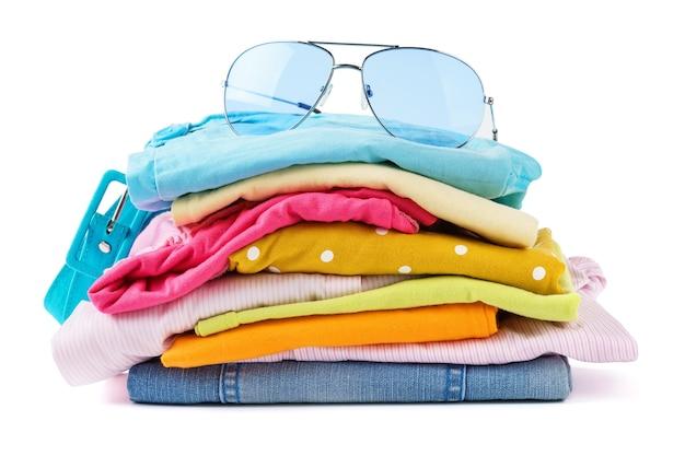 Pila di vestiti piegati su bianco isolato. abbigliamento e accessori estivi colorati.