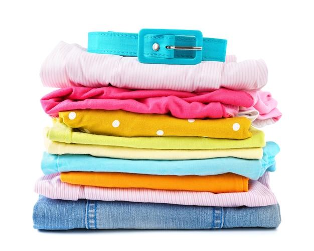 Pila di vestiti colorati piegati su bianco isolato. abbigliamento estivo moderno per bambini e ragazzi.