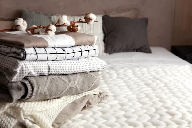 Pila di coperte calde piegate con diversi modelli di design e ramo di cotone su sfondo grigio. coperte lavorate a maglia. produzione di fibre tessili vegetali naturali. produzione. prodotto biologico