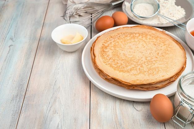 Pila di frittelle fritte, burro, uova e farina su una superficie chiara.