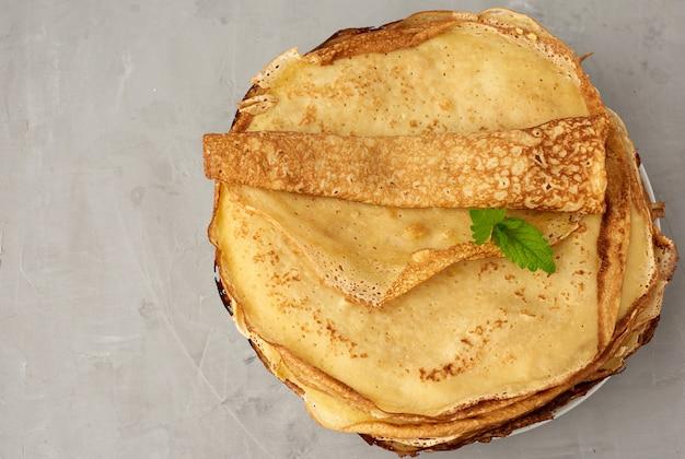 Pila di pancake rotondi fritti su un piatto