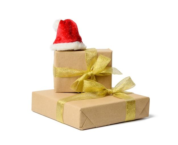 Pila di regali avvolti in carta kraft marrone e legati con nastro di seta, scatole isolate su sfondo bianco, elemento per designer