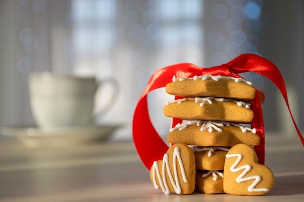 Pila di biscotti di pan di zenzero legati con nastro rosso e biscotto a forma di cuore in raggi di sole con tazza bianca e piatto sulla tavola di legno su fondo.