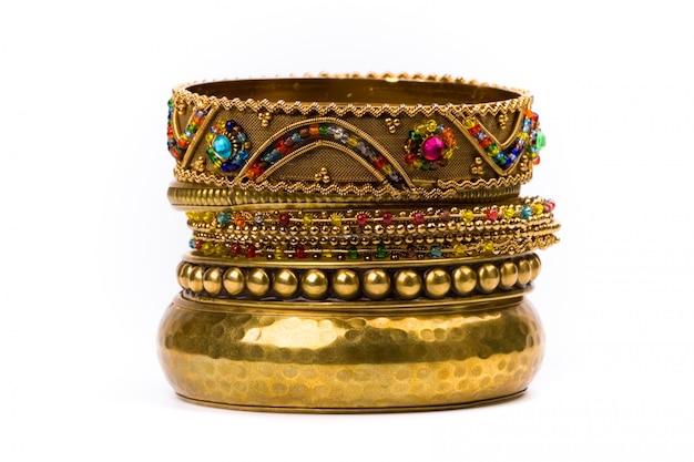 Pila di braccialetti d'oro isolato su sfondo bianco