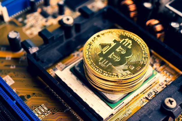 Pila di monete d'oro con il simbolo bitcoin su una scheda madre.