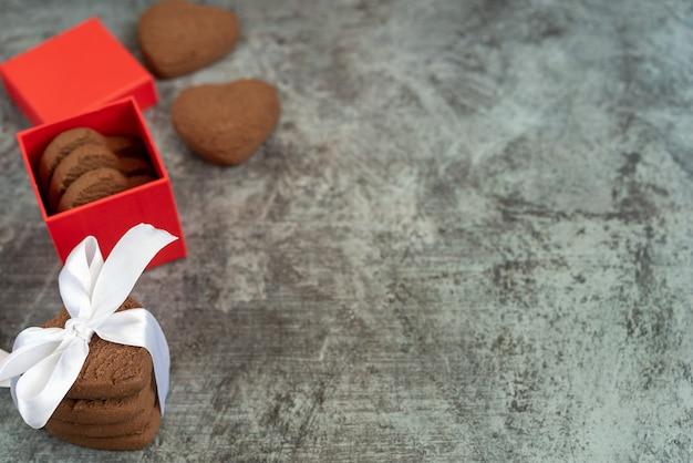 Pila di biscotti di pasta frolla a forma di cuore legati con nastro bianco e confezione regalo su sfondo grigio