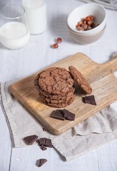 Una pila di biscotti al cioccolato fatti in casa con gocce di cioccolato, noci e un bicchiere di latte su un tavolo in legno chiaro. vista frontale
