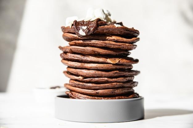 Pila di frittelle di cioccolato fatte in casa con mandorle tritate di cioccolato fuso e marshmallow