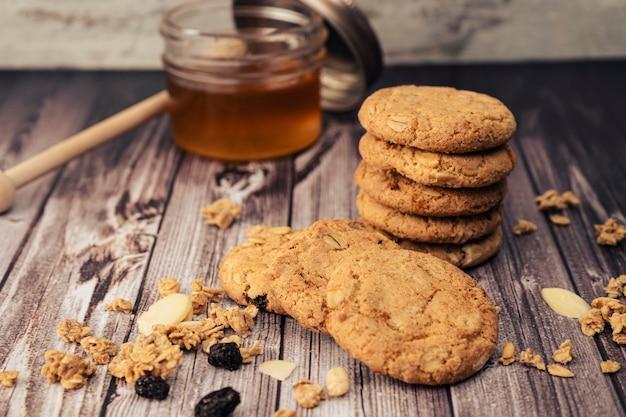 Pila di biscotti di farina d'avena fatti in casa e un vasetto di miele in background