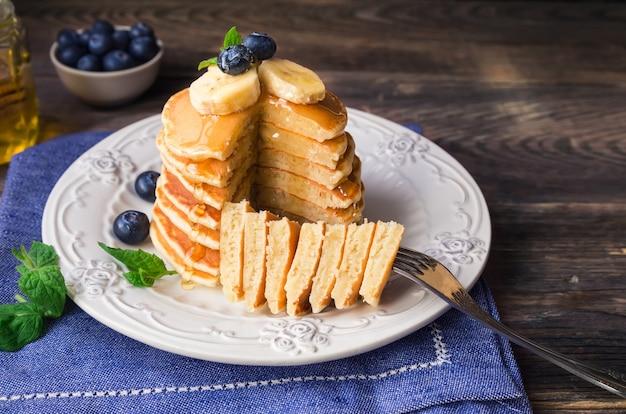 Pila di frittelle fatte in casa con mirtilli, banana e miele su legno rustico.