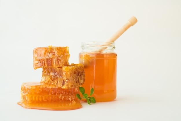 Pila di favi con erba e vaso di miele