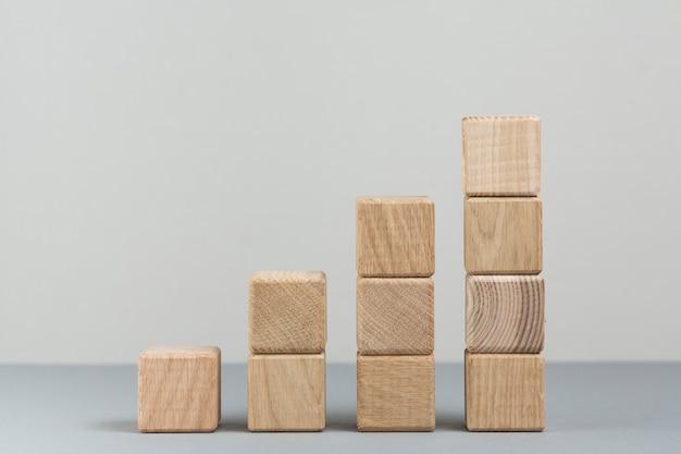 Pila di crescente blocco di legno su sfondo grigio