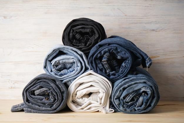 Pila di jeans in varie tonalità, i jeans sono impilati su uno sfondo di legno chiaro. trama di tela denim moda