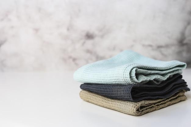 Stack asciugamani da cucina in cotone su sfondo grigio.