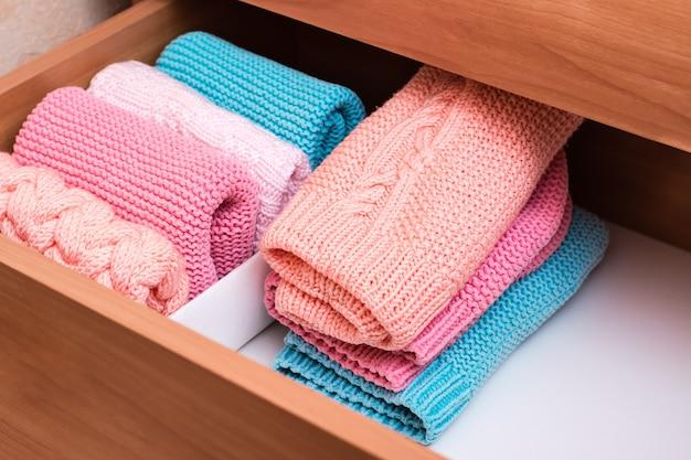 Una pila di vestiti a maglia accanto a una scatola di oggetti piegati in modo ordinato in un cassetto del comò.