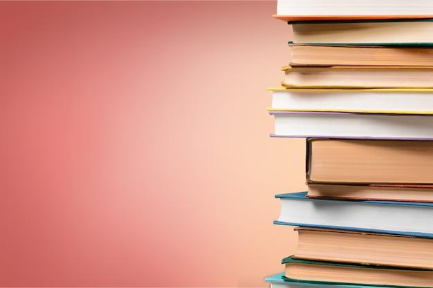 Pila di molti vecchi libri sullo scaffale nel negozio di libri o nella stanza della biblioteca con il fondo bianco della parete.
