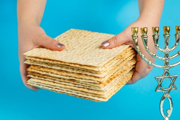 Una pila di matzo in mani femminili su una superficie blu vicino alla menorah