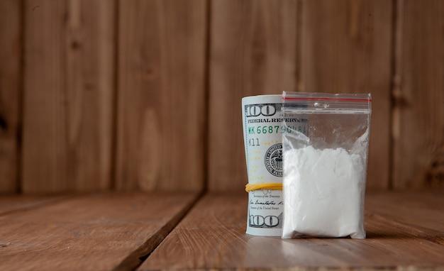 Pila di soldi e droghe su un tavolo di legno