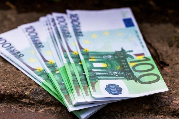 Una pila di soldi da cento euro giace sui gradini di pietra. foto di alta qualità