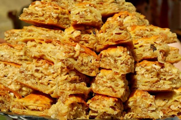 Pila di deliziosi pasticcini baklava che attirano le api affamate al mercato locale dell'armenia
