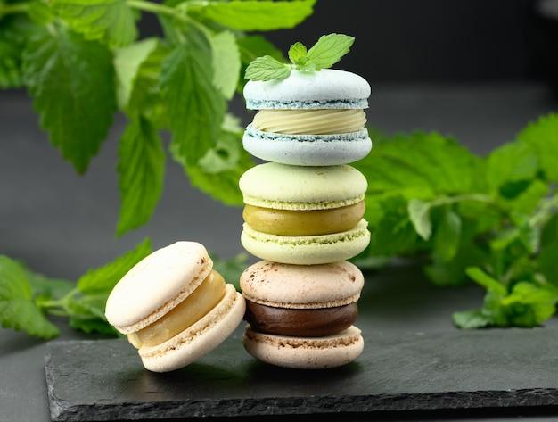 Pila di macarons multicolori su un fondo nero, dietro i rametti verdi di menta, un dessert delizioso e squisito