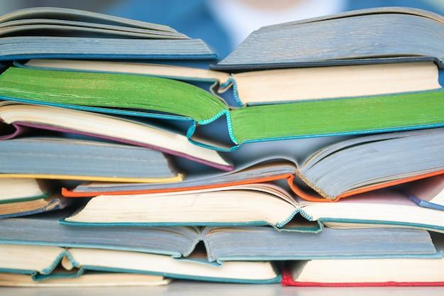 Pila di primo piano multicolore dei libri aperti, istruzione, lettura, di nuovo al concetto della scuola
