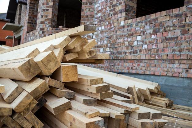 Pila di tavole di legno ruvide irregolari marroni naturali sul cantiere legname industriale per carpenteria, edilizia, riparazione e arredamento, materiale in legno per la costruzione di tetti.
