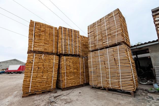 Pila di nuove tavole di legno e borchie presso il cantiere di legname. piatti di legno su pali per materiali d'arredamento