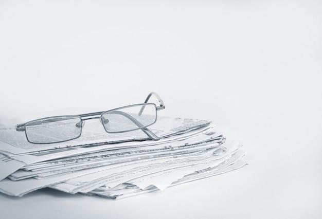 Pila di giornali e bicchieri isolati su bianco