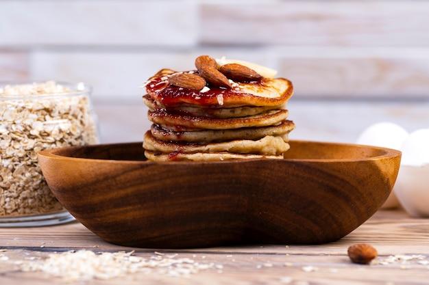 Pila di frittelle di avena con marmellata e mandorle in un piatto di legno
