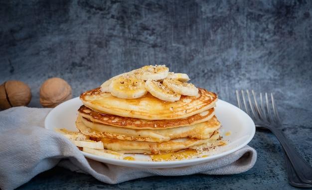 Pila di frittelle di banana di farina d'avena con fette di banana fresca, noci e miele su uno sfondo scuro. colazione salutare.