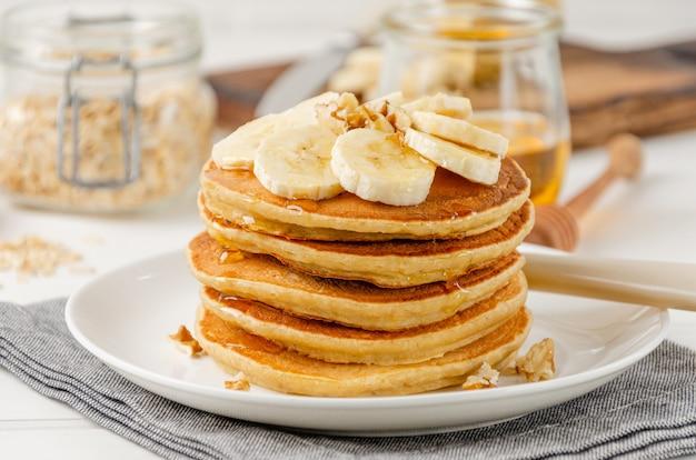 Una pila di frittelle di banana di farina d'avena con fette di banane fresche, noci e miele in cima con una tazza di tè