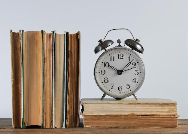 Pila di vecchi libri e sveglia sullo scaffale woden contro il muro bianco