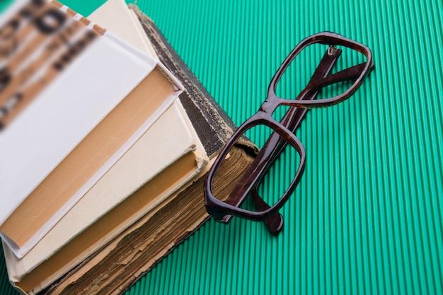 Pila di vecchi libri e montatura per occhiali su sfondo verde
