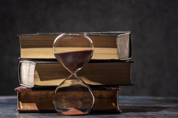 Una pila di libri antichi e una clessidra. il concetto di tempo e conoscenza.