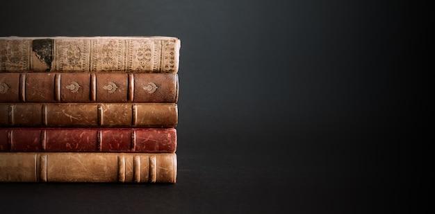 Pila di vecchi libri isolati su sfondo nero banner