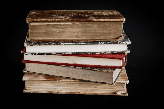 Pila di vecchi libri isolati su sfondo nero