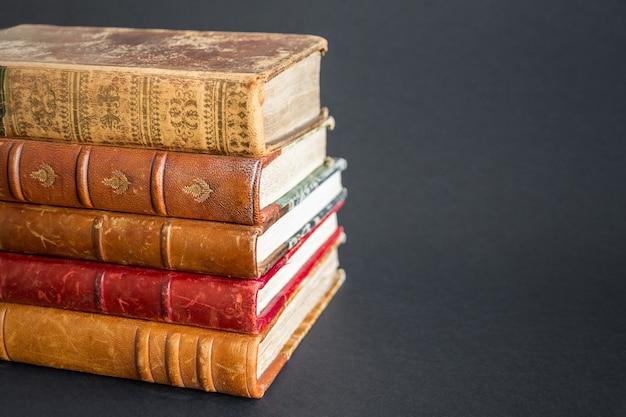 Pila di vecchi libri isolati su sfondo scuro