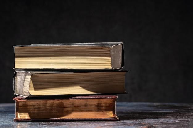 Una pila di vecchi libri sdraiati su un tavolo su uno sfondo scuro.