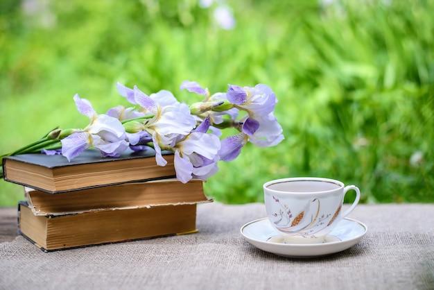 Una pila di vecchi libri, fiori viola iridi e una tazza di tè