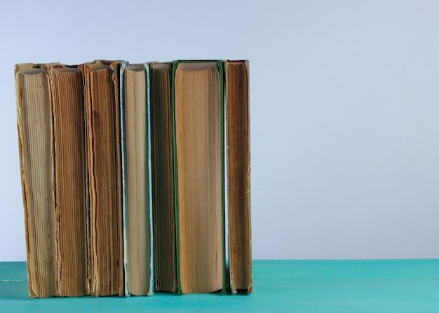Pila di vecchi libri su uno scaffale contro un muro bianco