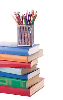 Pila di vecchi libri e un supporto con matite colorate isolate su bianco