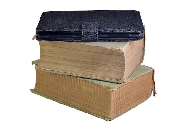 Pila di vecchi libri con libro elettronico su di esso, isolato su uno sfondo bianco.
