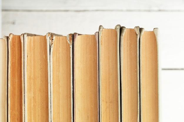 Pila di vecchi libri sullo scaffale di legno